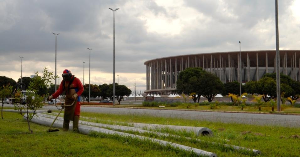 09.mai.2014 - Trabalhador corta a grama em rotatória ao lado de postes ainda não instalados para reforçar a iluminação no entorno do estádio Mané Garrincha, em Brasília: correria a um mês do início da Copa