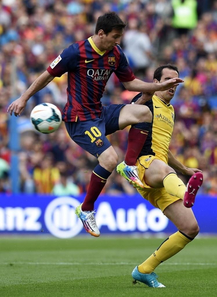 Messi, do Barcelona, divide bola com o uruguaio Diego Godin, do Atlético de Madri