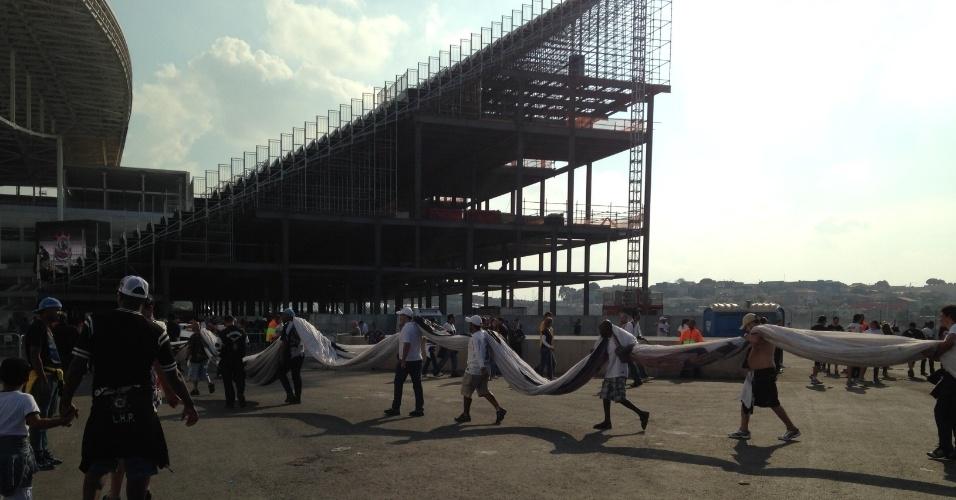 18.mai.2014 - Torcedores do Corinthians entram com bandeirão no Itaquerão em dia do primeiro jogo oficial do estádio
