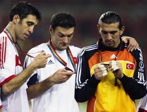 A Turquia ficou em 3° na Copa de 2002 com uma ótima equipe. Na imagem acima, aparecem Hakan Sukur (e), que marcou gol em 11 segundos na disputa de 3° lugar contra a Coreia do Sul, recorde de gol mais rápido em Copas; Alpay Ozalan, zagueiro que foi indicado à Fifa como candidato à seleção da Copa; e Rustu Recber (d), goleiro que fez defesas espetaculares durante todo o Mundial, inclusive nos dois jogos contra o Brasil