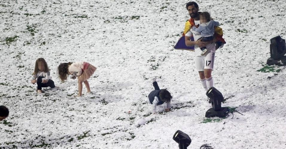25.mai.2014 - Arbeloa passeia com o filho, enquanto crianças no mar de papéis jogados no gramado do estádio do Real