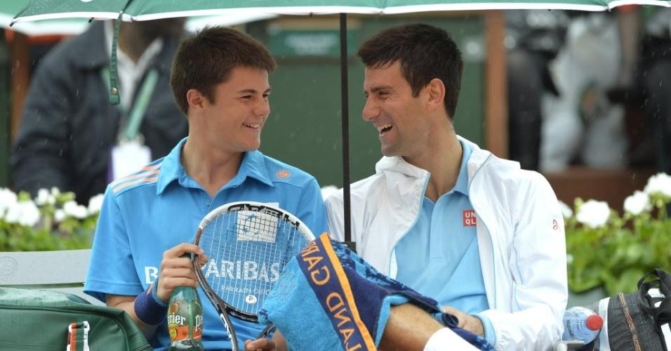 Novak Djokovic se diverte com um 'boleiro' durante partida contra João Sousa na sua estreia em Roland Garros