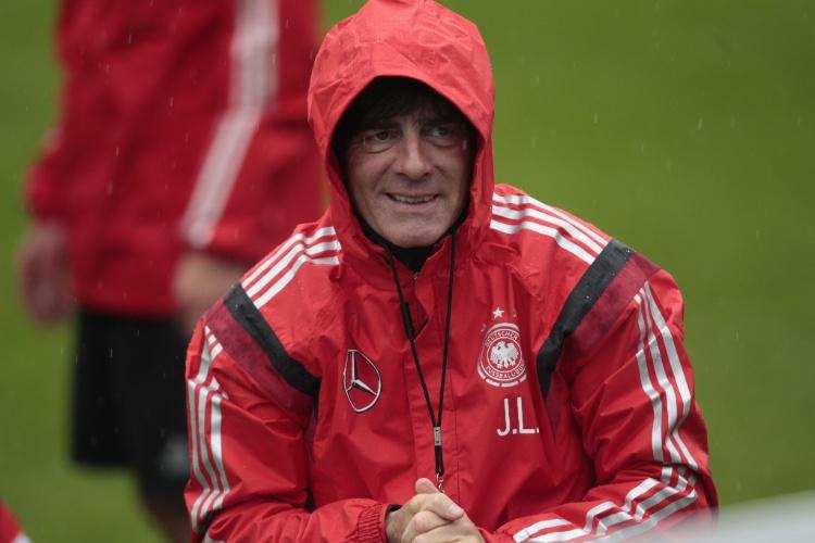27.mai.2014 - Técnico da Alemanha, Joachim Löw, se protege da chuva durante treino da seleção da Alemanha na Itália