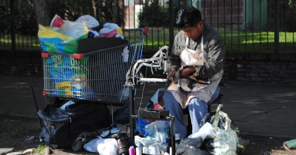 Sapateiro trabalha nas ruas pobres e sujas do bairro onde nasceu Carlito Tevez