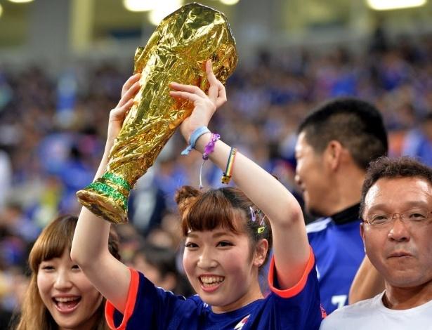 27.mai.2014 - Torcedora levanta réplica da Taça do Mundo em amistoso entre Japão e Chipre, realizado em Saitama