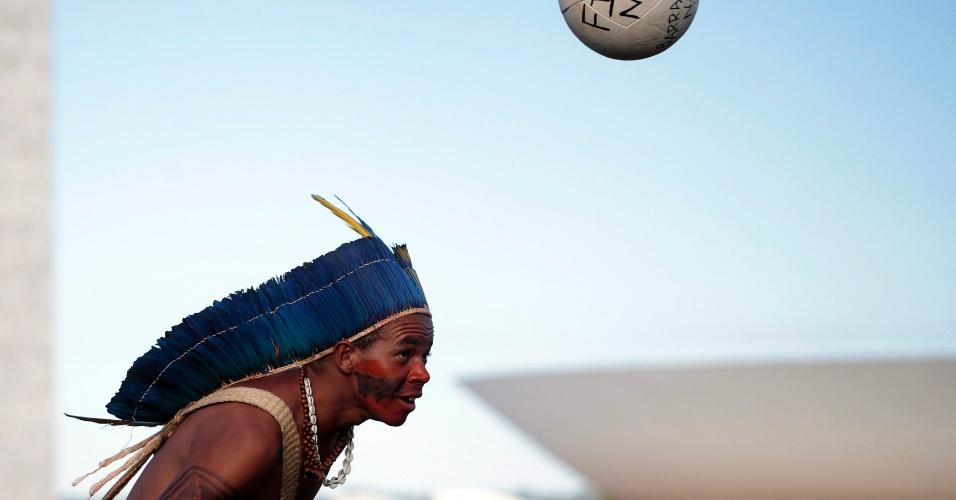 """28.mai.2014 - Índio cabeceia bola """"Fifa Não"""" durante protesto em Brasília"""