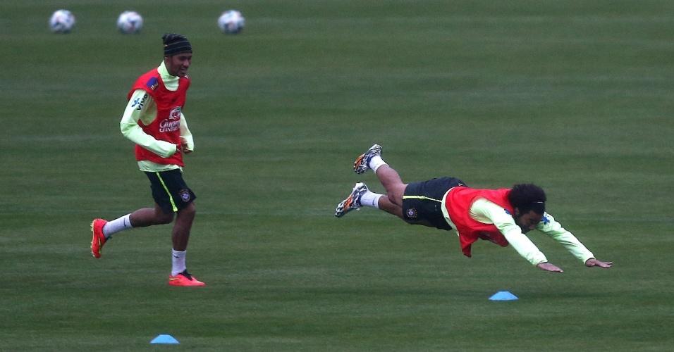 28.mai.2014 - Neymar sorri enquanto Marcelo salta no gramado da Granja Comary