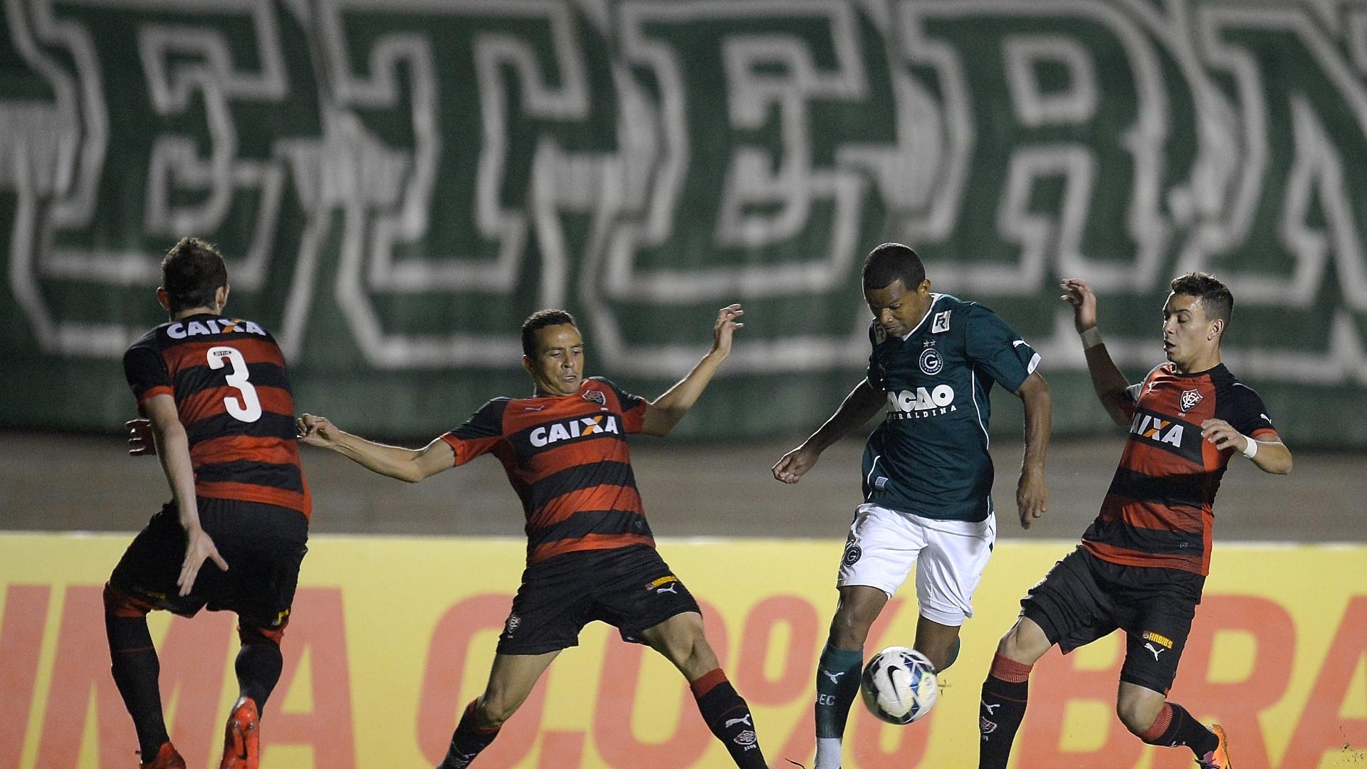 28.mai.2014 - Vitor, do Goiás, passa entre dois jogadores do Vitória no duelo no Serra Dourada