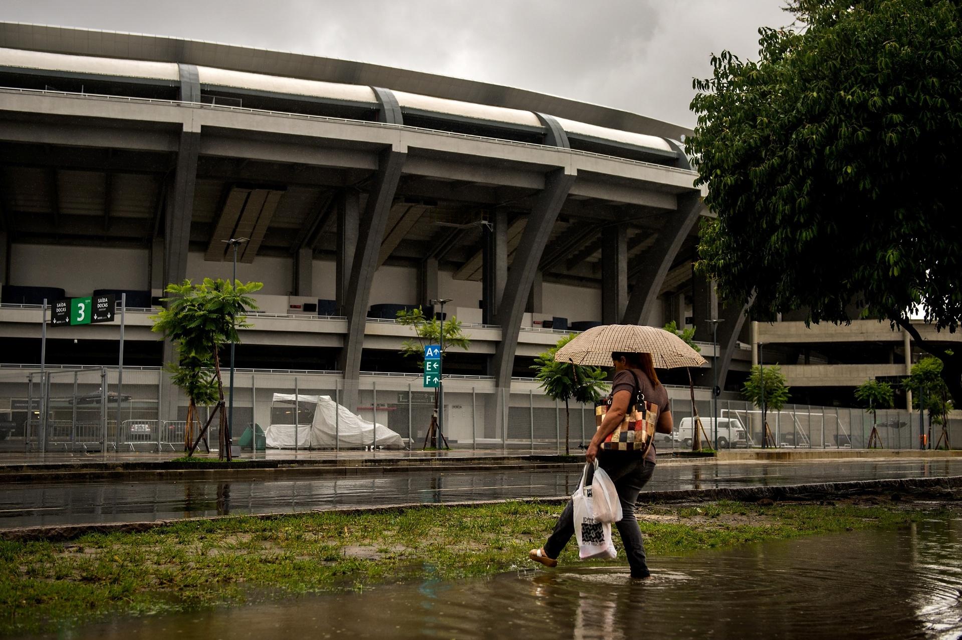 Maracanã: detalhe de mulher passando por área alagada no entorno do estádio