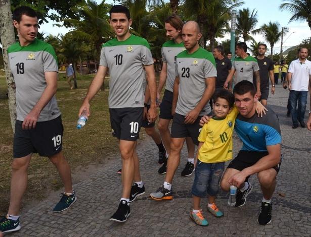 garotinha com camisa do brasil posa para foto com jogador da seleção australiana, em Vitória-ES