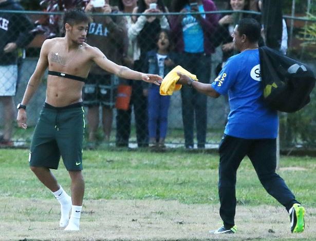 """30.05.14 - Neymar troca agasalho por camiseta regata no treino na seleção; mini strip-tease do atacante fez a alegria das """"neymarzetes"""" presentes na Granja"""