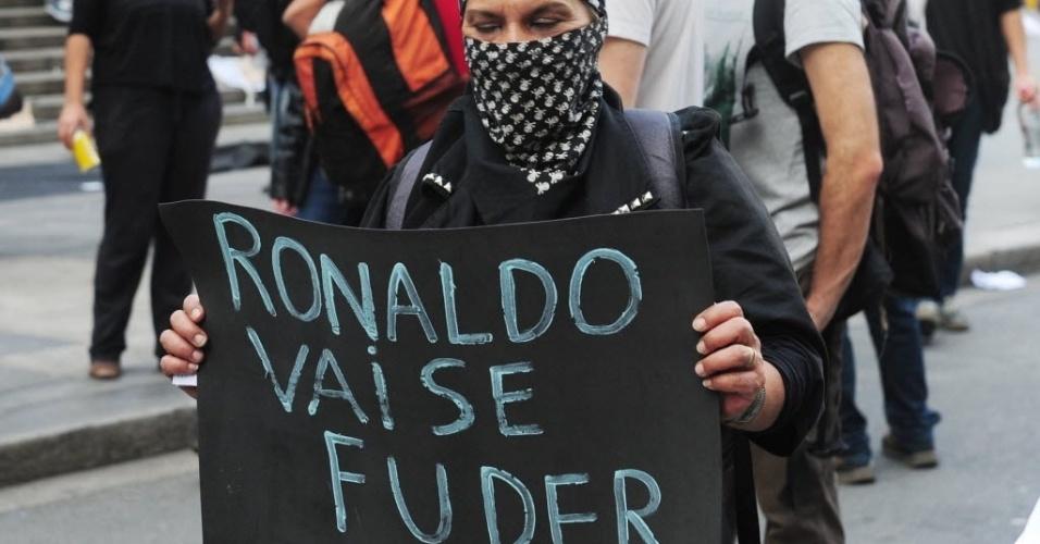 31.mai.2014 - Manifestante com o rosto coberto leva cartaz contra Ronaldo em protesto realizado em São Paulo
