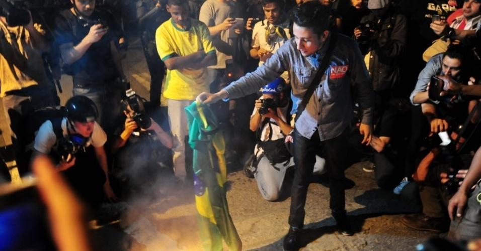 31.mai.2014 - Manifestante queima a bandeira do Brasil durante protesto contra a Copa do Mundo em São Paulo