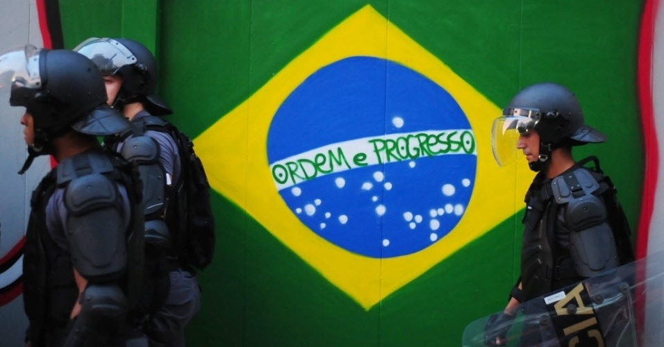 31.mai.2014 - Policiais passam por bandeira do Brasil durante protesto contra a Copa em São Paulo