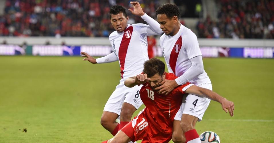 Atacante Admir Mehmedi, da Suíça, é derrubado por Rinaldo Cruzado e Alexander Callens, do Peru, durante amistoso em Lucerna