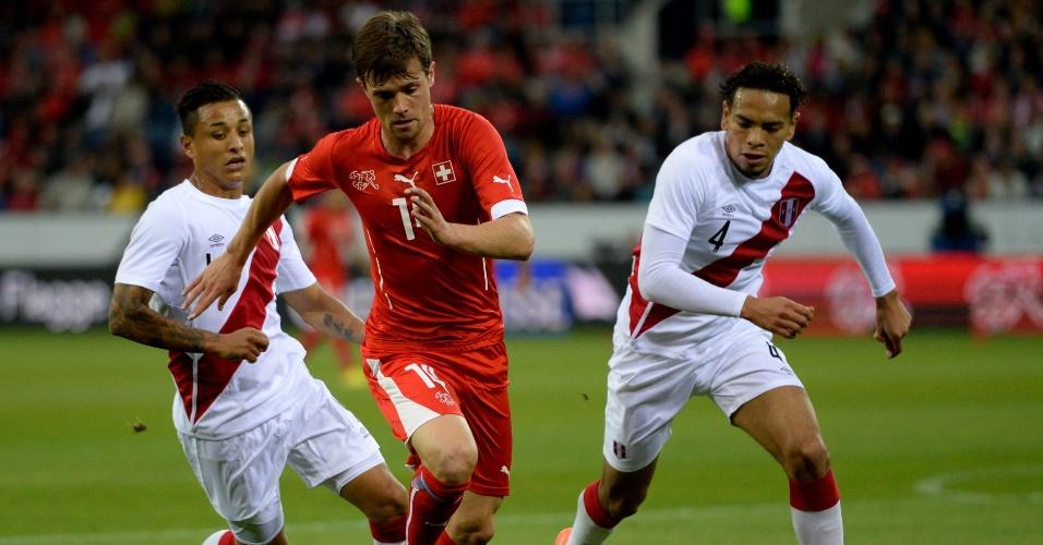 Valentin Stocker, da Suíça, é cercado por Alexander Callens, do Peru, em amistoso disputado em Lucerna