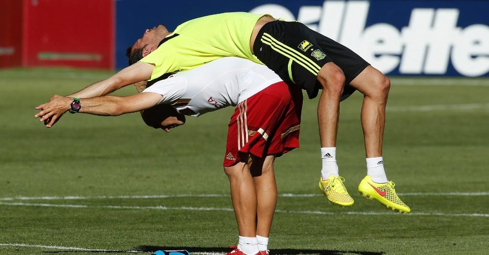 06.jun.2014 - Volante Sergio Busquets alonga as costas com ajuda de preparador físico durante treinamento da seleção espanhola nos Estados Unidos