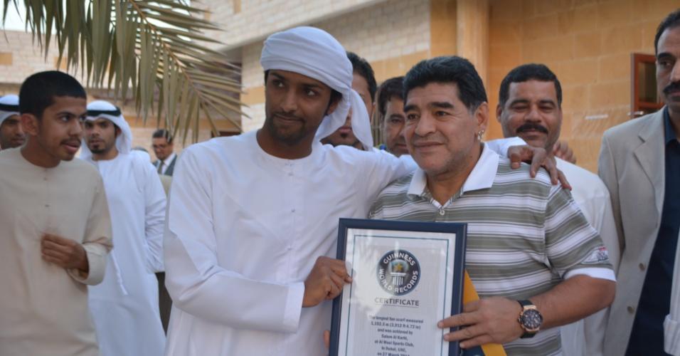 Salem Al-Karbi posa com o astro argentino Diego Armando Maradona e com o certificado do maior cachecol de um time de futebol, registrado pelo livro dos recordes