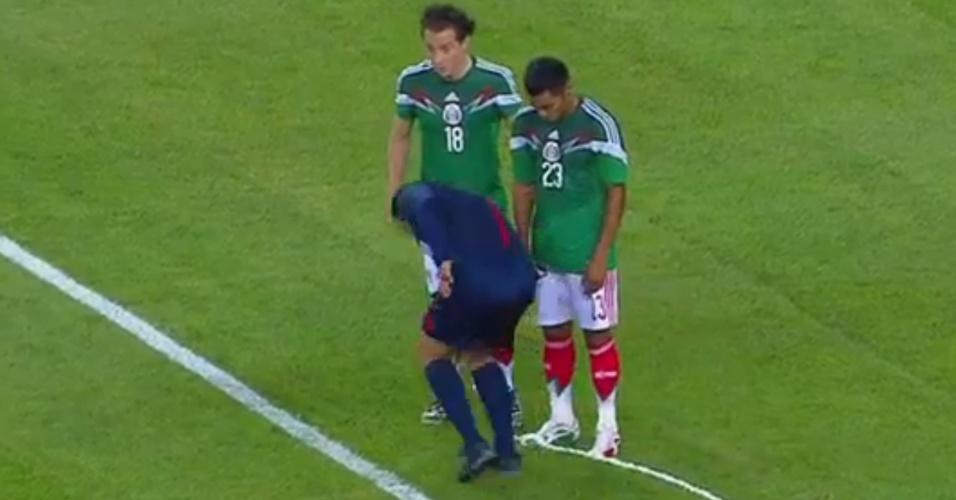 Árbitro passa spray em pé de jogadores para evitar que barreira ande