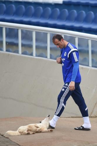 Goleiro Asmir Avdukic, da Bósnia-Herzegovina, observa cachorra antes de treino no estádio Municipal Antonio Fernandes, no Guarujá