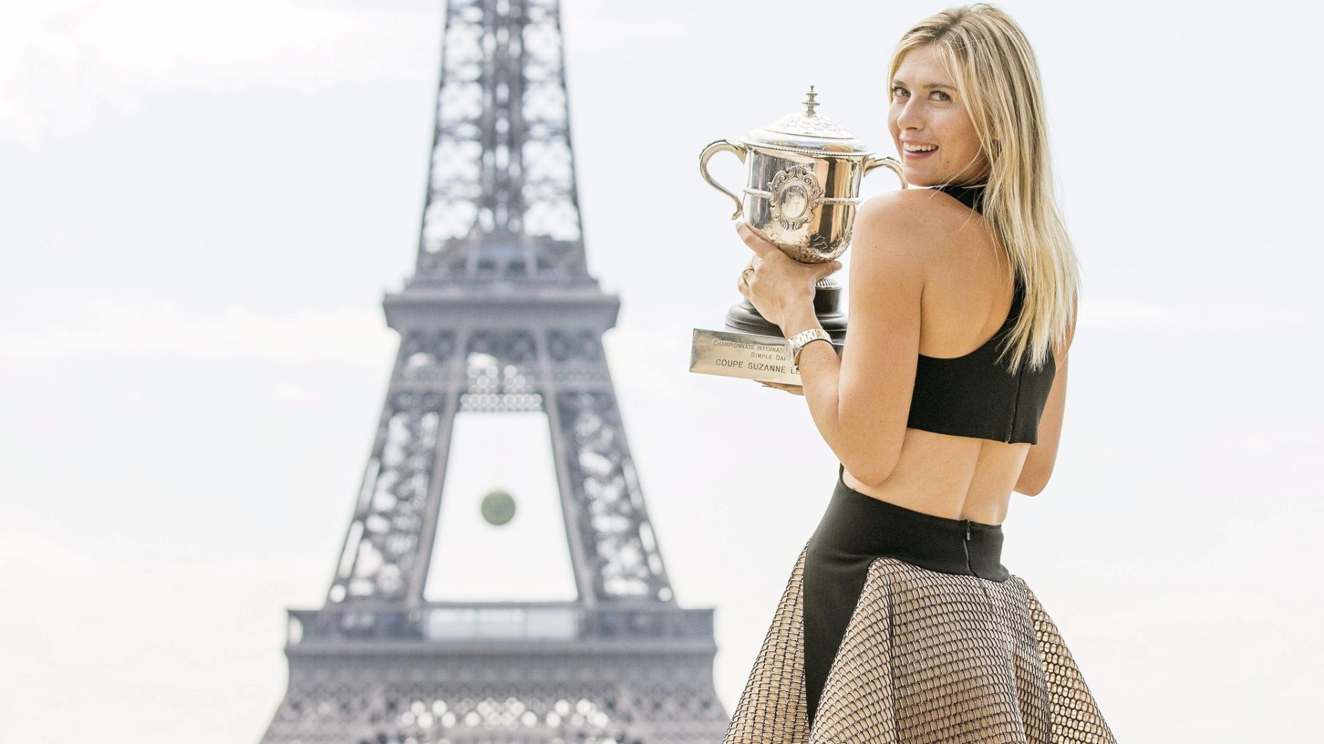 08.jun.2014 - Bicampeã do torneio feminino, Maria Sharapova posa com troféu de Roland Garros em frente à Torre Eifel