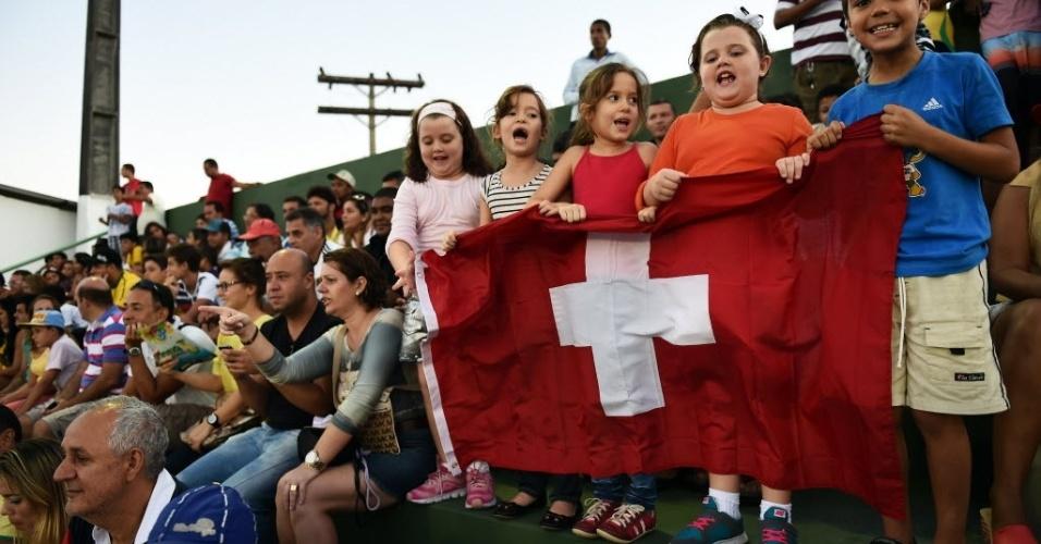 Crianças seguram uma bandeira durante treino da Suíça, em Porto Seguro