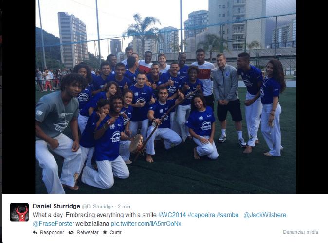 """09. jun. 2014 - Daniel Sturridge (4º da dir. para a esq.), da Inglaterra, posta foto com grupo de capoeira na favela da Rocinha; """"Que dia... abraçando todos com um sorriso"""", escreveu o atacante"""