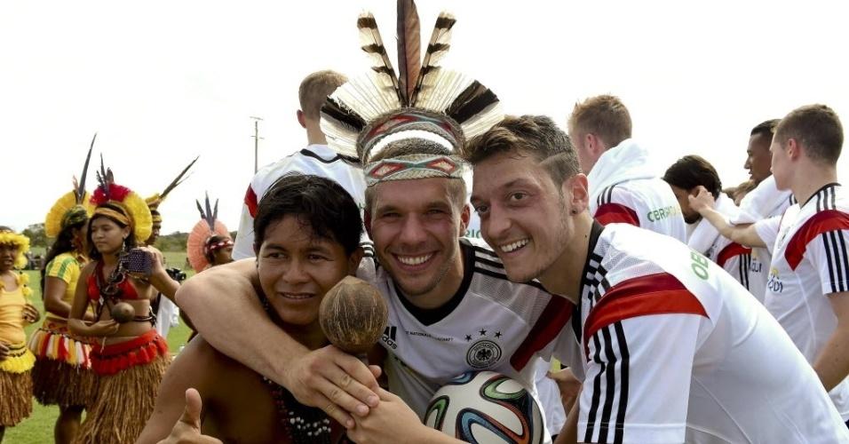 09. jun. 2014 - Podolski e Özil posam para foto com integrante do grupo de dança indígena, que fez apresentação especial para a seleção alemã nesta segunda-feira