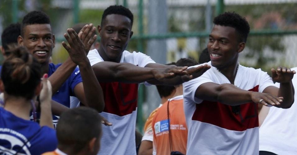 Danny Welbeck e Daniel Sturridge, da seleção inglesa, dançam com jovens da favela da Rocinha, no Rio de Janeiro