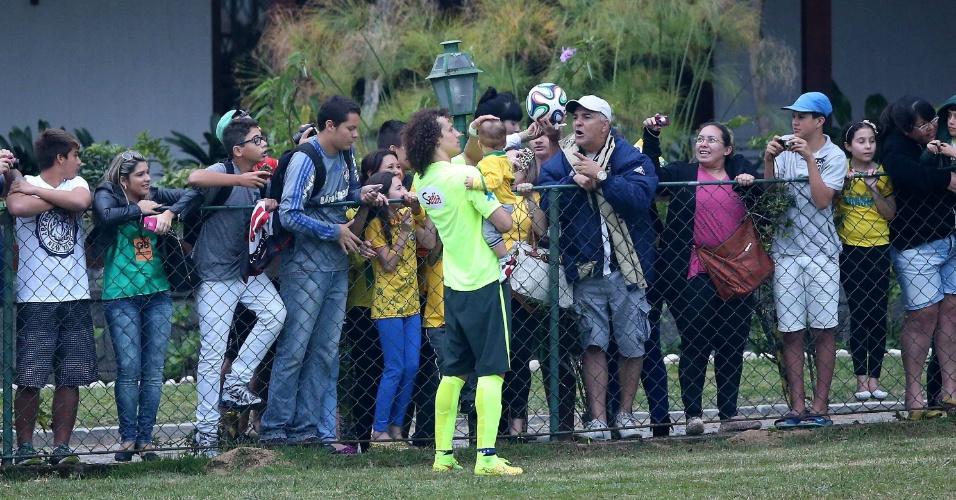 David Luiz segura bebê no colo enquanto conversa com torcedores na Granja Comary