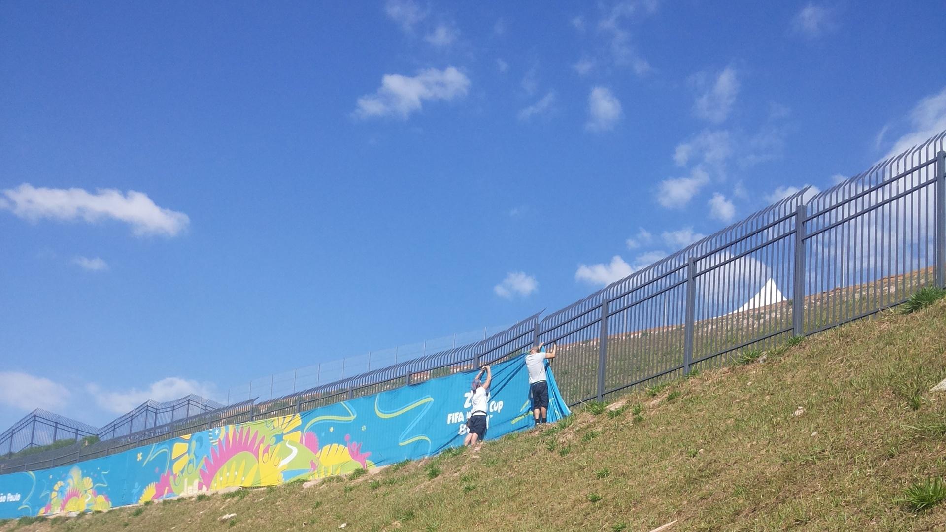 Funcionários prendem faixa da Copa do Mundo no entorno do Itaquerão, estádio que receberá a abertura do torneio