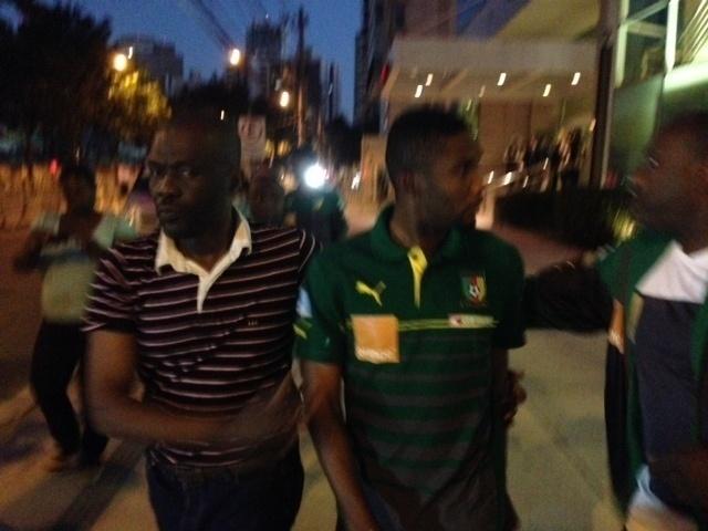 Samuel Eto'o é acompanhado por seguranças enquanto a delegação de Camarões se encaminha para a praia