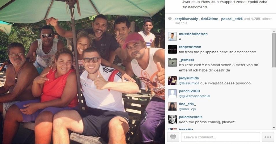 10.jun.2014 - Atacante da Alemanha, Lukas Podolski posa ao lado de fãs em Santa Cruz de Cabrália, na Bahia