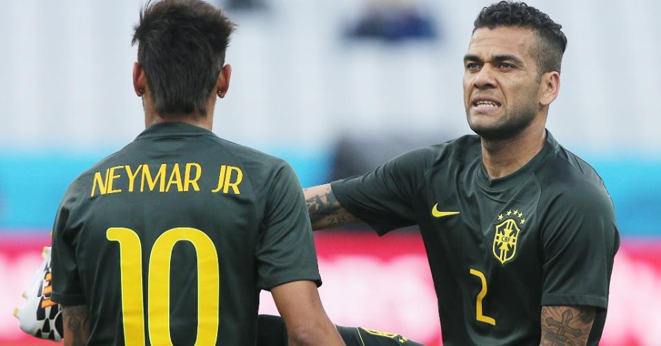 11.jun.2014 - Neymar ajuda Daniel Alves a se alongar durante atividade realizada no Itaquerão