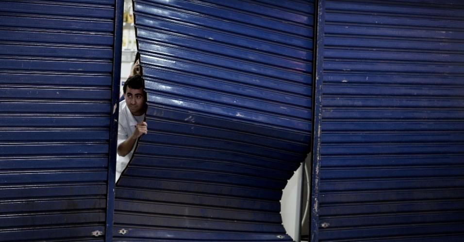 12.06.14 - Homem observa porta danificada de comércio após protesto em Belo Horizonte