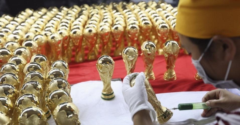 12.jun.2014 - Em Dongguan, na China, trabalhador confecciona pequenas réplicas do troféu de campeão da Copa do Mundo
