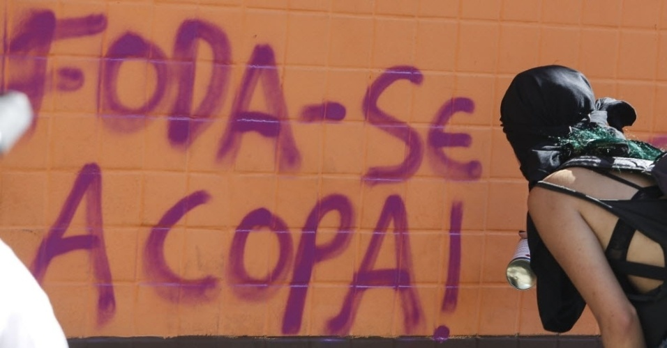 12.jun.2014 - Manifestante picha o muro e manda recado contra a Copa do Mundo