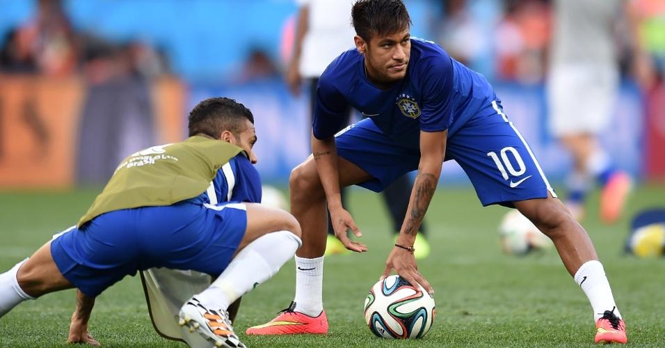 12.jun.2014 - Neymar e Daniel Alves fazem aquecimento para a estreia do Brasil na Copa