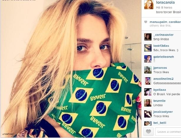Carolina Dieckmann colocou uma máscara com bandeiras brasileiras para torcer pela seleção de Felipão