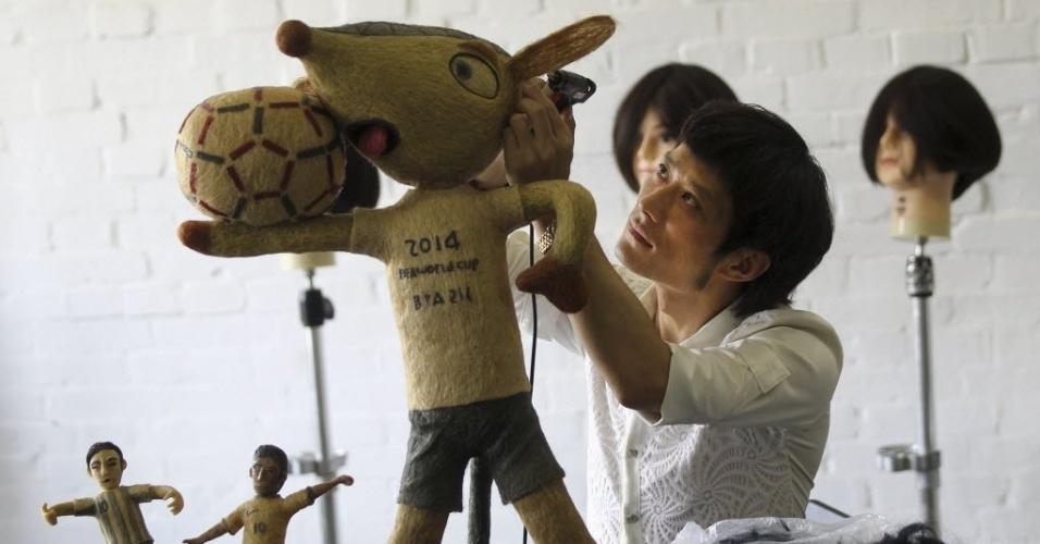 12.jun.2014 - Em Pequim, artesão chinês desenvolve um boneco do Fuleco, mascote oficial da Copa do Mundo no Brasil