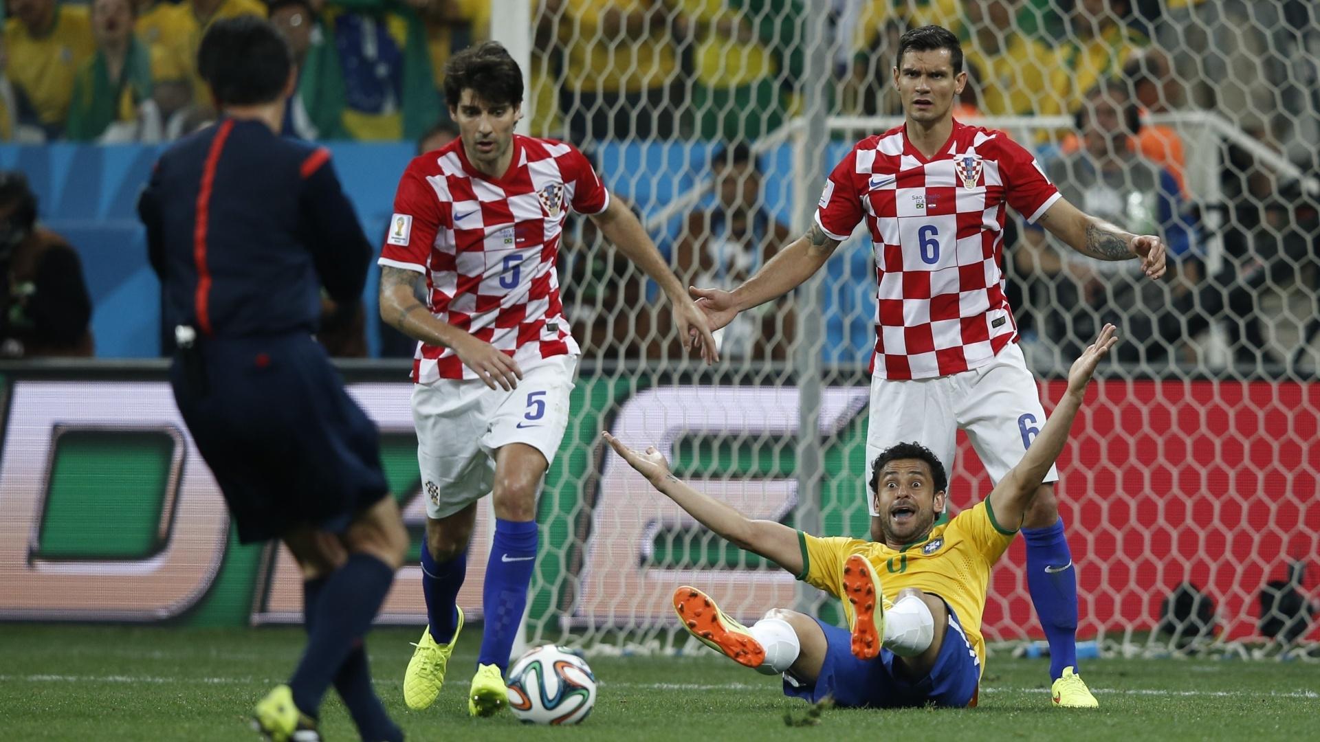 12.jun.2014 - Fred é derrubado na área, pede pênalti e o árbitro Yuichi Nishimura marca, para revolta dos jogadores croatas