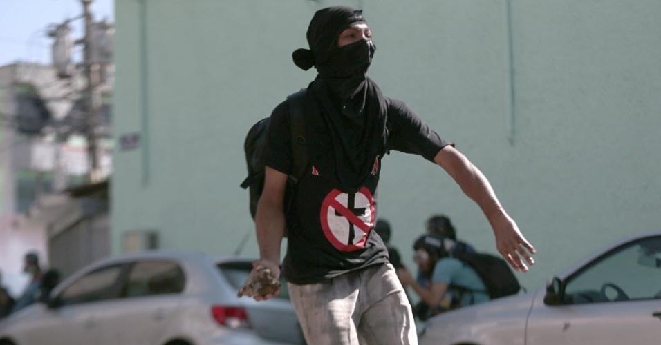 Manifestante se prepara para arremessar pedra na direção da polícia durante manifestação em São Paulo