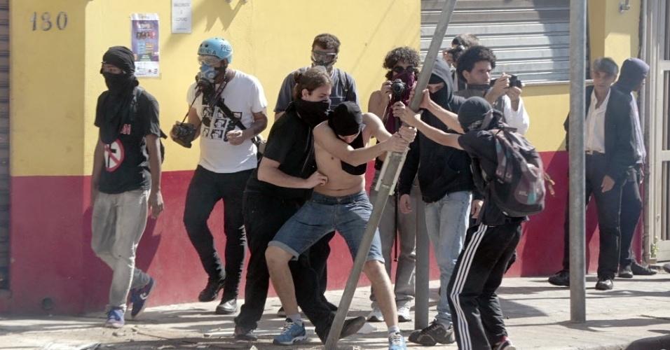 Manifestantes causam estragos nas ruas durante protesto que terminou em confronto contra a polícia