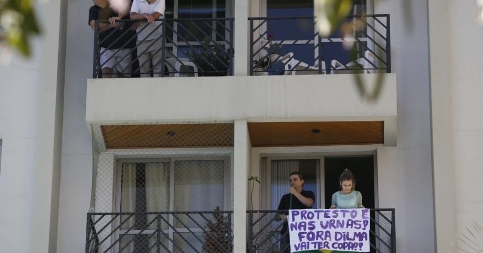 """Na sacada de um prédio, casal exibe faixa criticando os protestos em São Paulo e a presidente Dilma: """"Protesto é nas urnas! Fora Dilma. Vai ter Copa"""""""