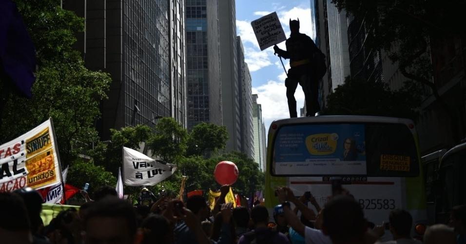 Vestido de Batman, manifestante sobe em cima de ônibus no Rio de Janeiro e exibe cartaz pedindo para que o Brasil seja campeão na saúde e na educação