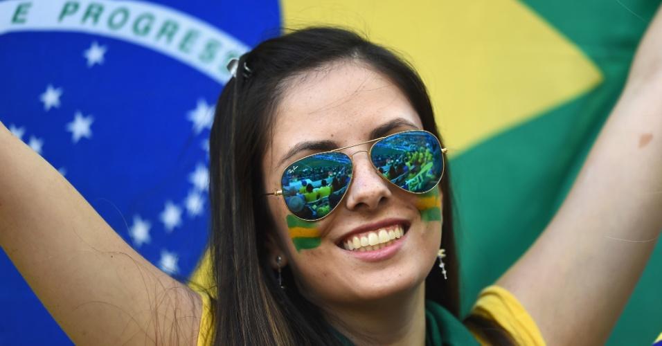 12.jun.2014 - Torcedora pinta o rosto com as cores do Brasil
