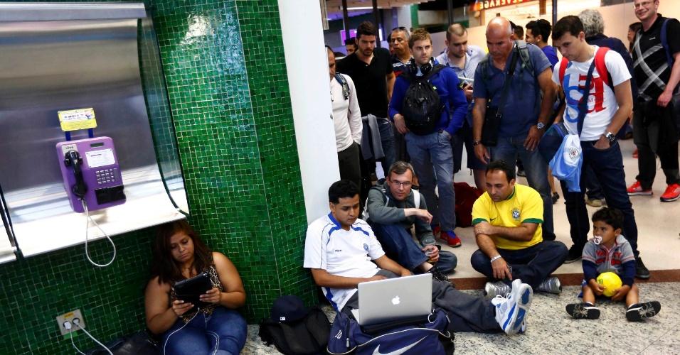 13.jun.2014 - Pessoas se reúnem em um canto do aeroporto de São Paulo para assistir à partida entre Camarões e México em um Laptop