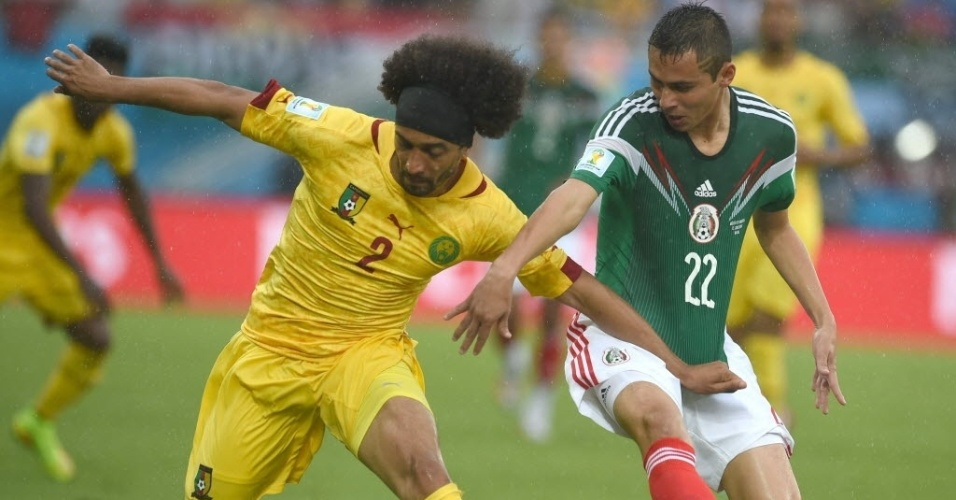 Benoit Assou-Ekotto e Paul Aguilar se empurram para ficar com a bola na partida entre México e Camarões