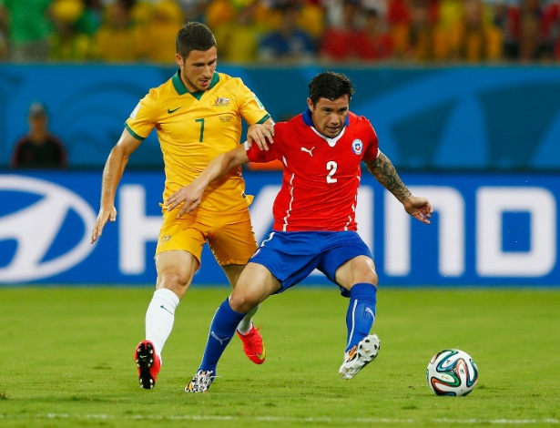 13.jun.2014 - Mathew Leckie, da Austrália, marca de perto Eugenio Mena, do Chile, na partida na Arena Pantanal
