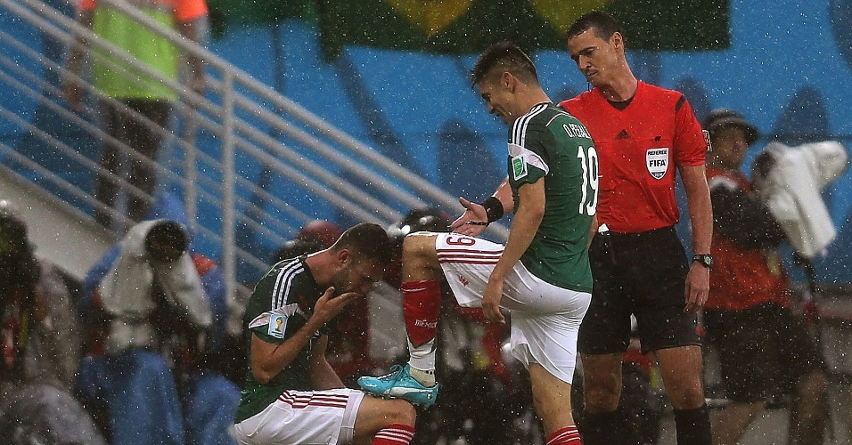 Miguel Layun beija a chuteira de Peralta após o atacante fazer o único gol da partida entre México e Camarões